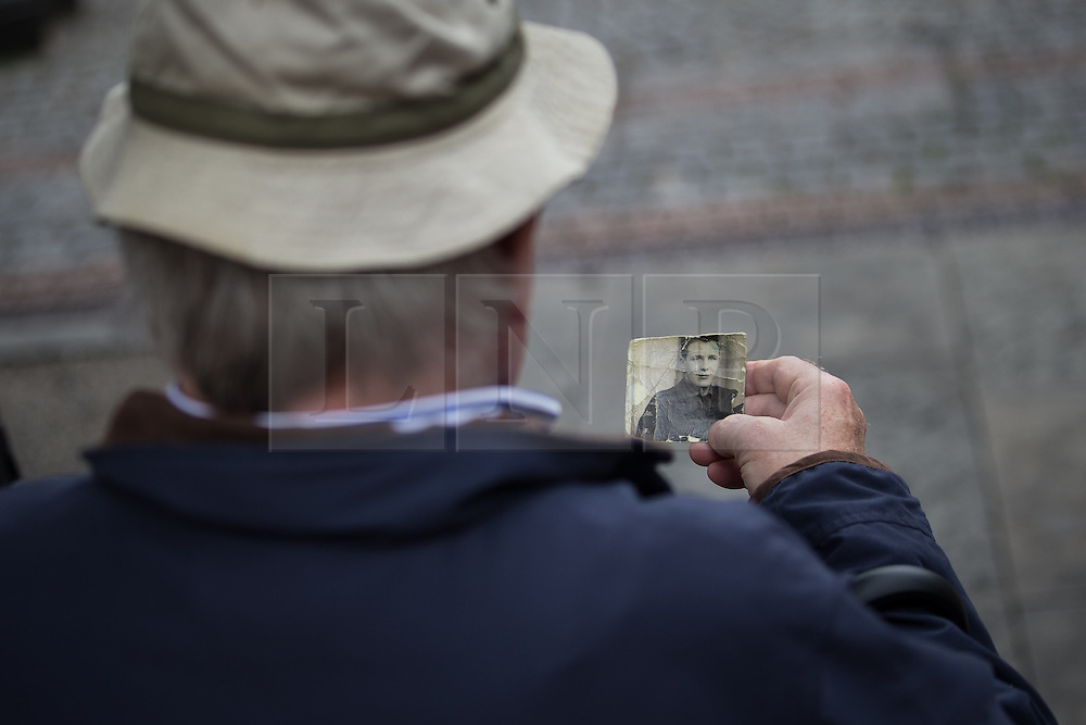 © Licensed to London News Pictures . 01/07/2016 . Manchester , UK .  A man sitting on a bench in Albert Square , looking at an old photo . Somme100 events in Manchester City Centre to commemorate the 100th anniversary of the first day of the Battle of the Somme . Photo credit : Joel Goodman/LNP