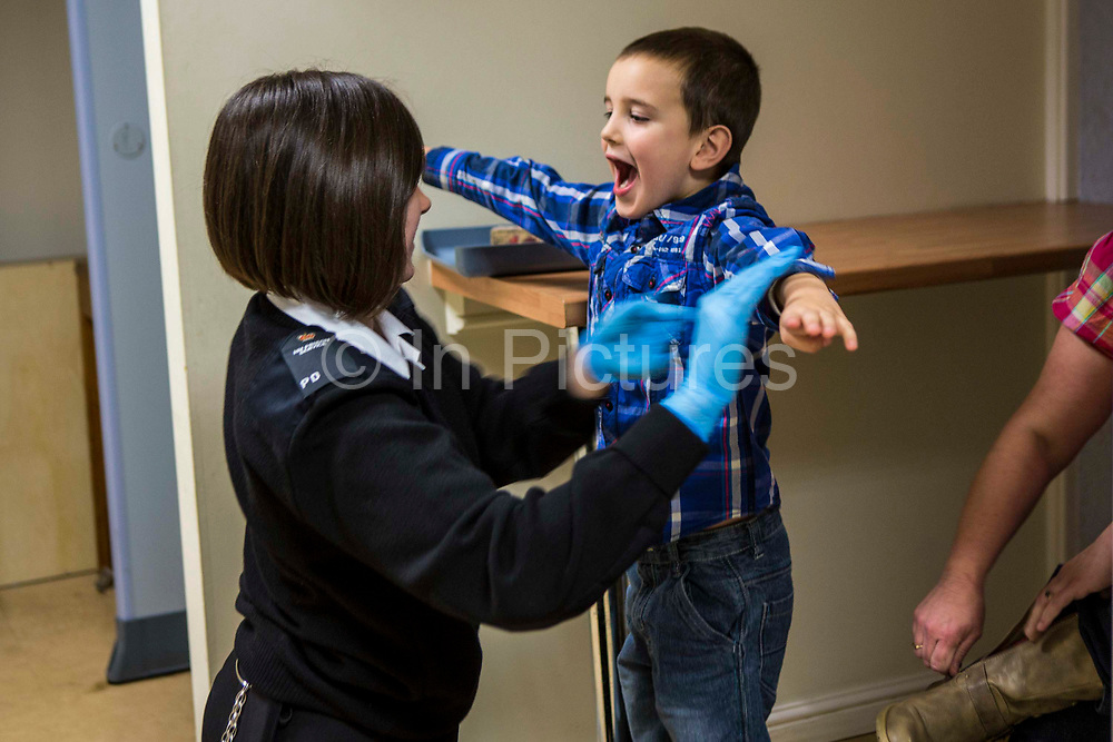 The child of a prisoner go through the search process to get into a family visit session. HMP/YOI Portland, Dorset. A resettlement prison with a capacity for 530 prisoners. Dorset, United Kingdom.
