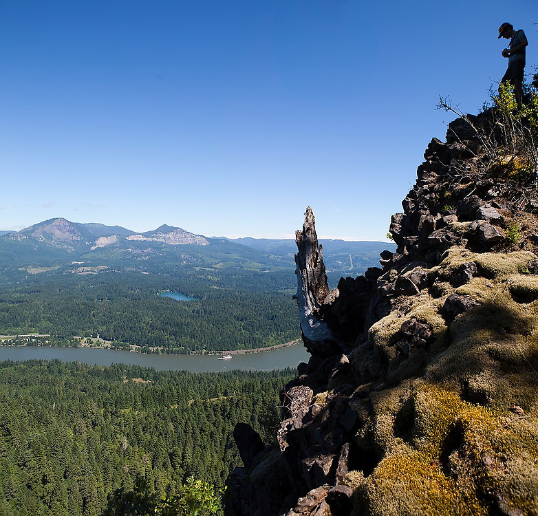 Hiker Hamilton Boyce stands silhouetted on the edge of a high cliff overlooking the Columbia River Gorge from the Ruckel Creek Trail in Oregon's Columbia River Gorge National Scenic Area. The Columbia Gorge Sternwheeler, operated by Portland Spirit, paddles up the river on a scenic cruise.