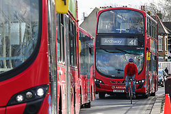 © Licensed to London News Pictures. 11/02/2020. London, UK. A cyclist and buses on high road in north London as Prime Minister, BORIS JOHNSON announces £5 billion new funding to improve bus services and cycle lanes across the country, which will transform with simpler fares, thousands of new buses, improved routes and higher frequencies. There will be at least 4,000 new Zero Emission Buses to make greener travel, driving forward the UK's progress on its net zero ambitions. Photo credit: Dinendra Haria/LNP
