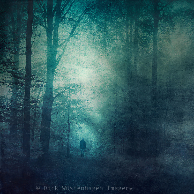 Man going towards a light tunnel in a forest. <br /> Texturized & manipulated photograph