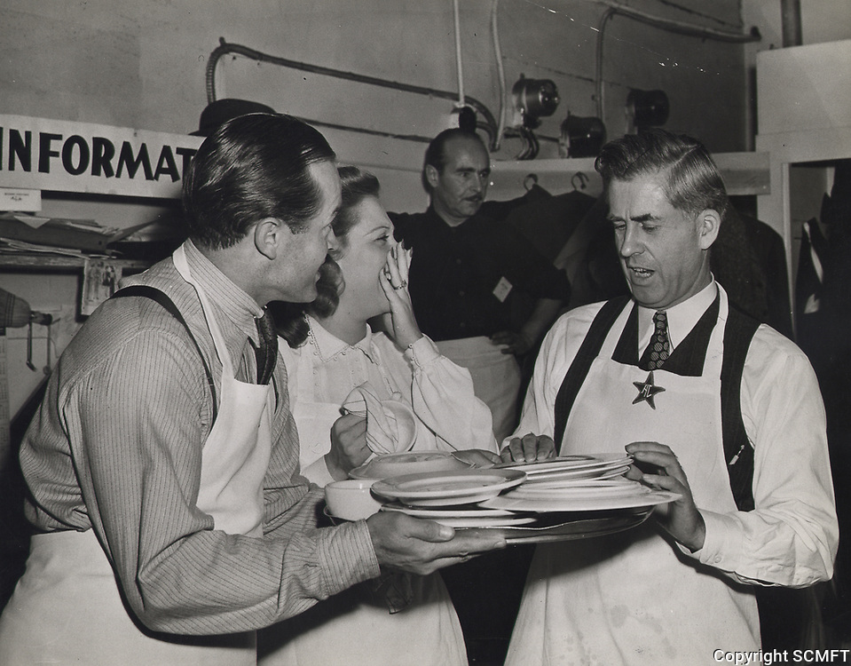 1944 Dinah Shore laughs as Bob Hopes hands U.S. Vice President, Henry Wallace, a tray of dirty dishes to wash.