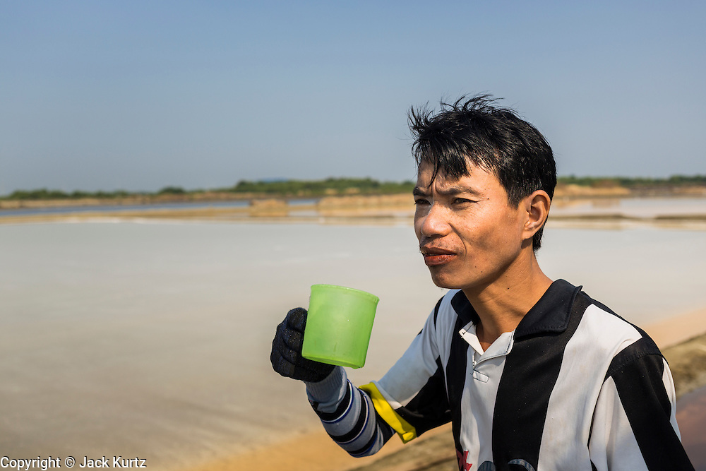 """28 MARCH 2014 - NA KHOK, SAMUT SAKHON, THAILAND: A Burmese migrant laborer drinks a glass of water during a break on a Thai salt farm in Samut Sakhon province. Thai salt farmers south of Bangkok are experiencing a better than usual year this year because of the drought gripping Thailand. Some salt farmers say they could get an extra month of salt collection out of their fields because it has rained so little through the current dry season. Salt is normally collected from late February through May. Fields are flooded with sea water and salt is collected as the water evaporates. Last year, the salt season was shortened by more than a month because of unseasonable rains. The Thai government has warned farmers and consumers that 2014 may be a record dry year because an expected """"El Nino"""" weather pattern will block rain in mainland Southeast Asia. Salt has traditionally been harvested in tidal basins along the coast southwest of Bangkok but industrial development in the area has reduced the amount of land available for commercial salt production and now salt is mainly harvested in a small parts of Samut Songkhram and Samut Sakhon provinces.    PHOTO BY JACK KURTZ"""