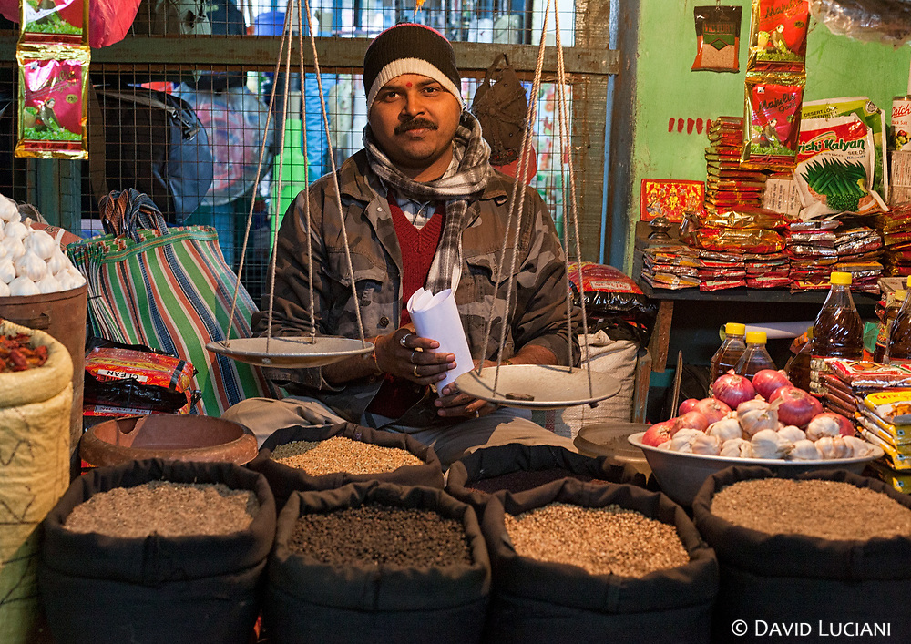 An Indian man selling primarily spices in his stall in Pasighat.