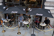Three tables for 3 pairs of customers sitting very close to one another outside Caffe Concerto on Piccadilly at the 6-month milestone of the Coronavirus pandemic lockdown, 24th September, in London, England. New restrictions are being re-introduced by the government after a sudden climb in the Covid infection rate, a predicted 'second spike'.