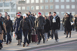 © Licensed to London News Pictures. 25/02/2016. London, UK. Commuters walk across London Bridge during cold winter weather and freezing temperatures this morning. Following a mild spell, weather forecasters are predicting a spell of very cold weather, with widespread morning frosts and freezing temperatures which are predicted to last up to the weekend. Photo credit : Vickie Flores/LNP