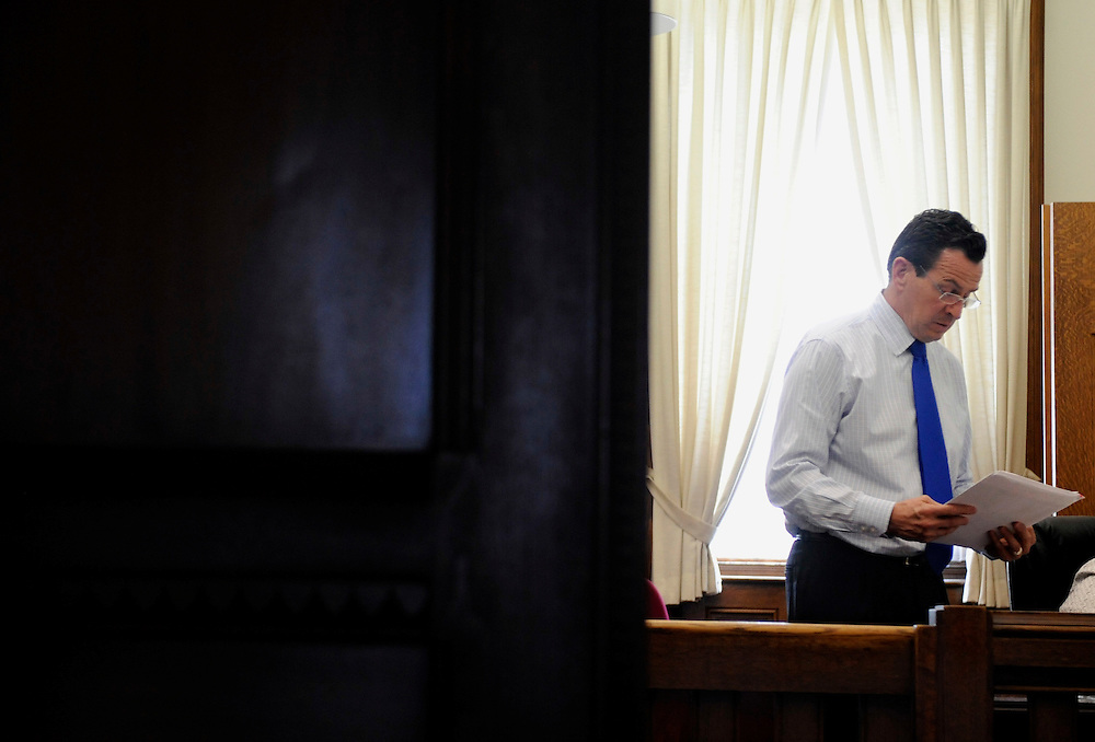 Gov. Dannel P. Malloy, looks over paperwork in his office at the Capitol in Hartford, Conn., Tuesday, May 10, 2011.  Malloy said his administration is beginning the process Tuesday of issuing 4,742 layoff notices to Connecticut state employees because a two-year, $2 billion labor savings deal has not yet been reached with unionized workers.   (AP Photo/Jessica Hill)