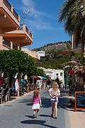 Two sisters hiding their ice cream, Sant Elm, Mallorca, Balearic Islands, Spain