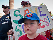 27 JUNE 2009 -- PHOENIX, AZ: A child with a sign during a march at the Arizona state capitol Saturday. Arizona has the second worst state budget deficit in the country (only California's is worst) and the Republican controlled legislature is threatening to balance the budget by making massive cuts in social and education spending while cutting taxes. Small numbers of public school teachers and parents of public school students have been marching on the capitol almost every day of the week but Saturday's march, with well over 500 people was the largest of session. The legislature and Gov. Jan Brewer, also a Republican, are deadlocked in negotiations and the Governor has threatened to shut down state government on July 1 if there is no budget. Republican leaders in the legislature are threatening to present the Governor with a budget, without input from the Governor's office, at midnight on June 30, forcing her to sign the budget to keep the state open.  Photo by Jack Kurtz