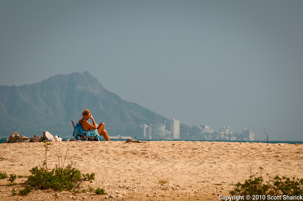 A man sitting in a beach chair on Sand Island in front of Diamond Head.