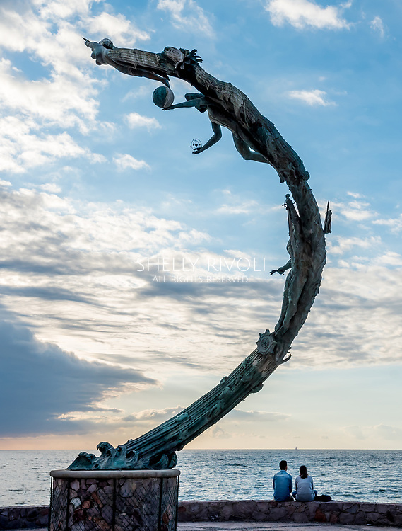 On the malecon a couple watches the sunset over Bay of Banderas with El Milenio (The Millennia) sculpture by artist Mathis Lidice arching above them into the clouds.