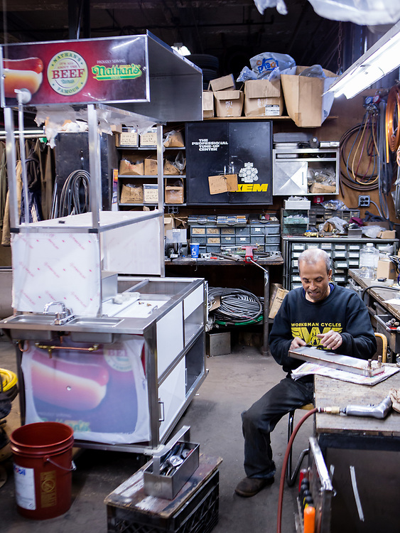 Jasim Uddin filing rough edges on a water heater for a food cart for Nathan's Famous.