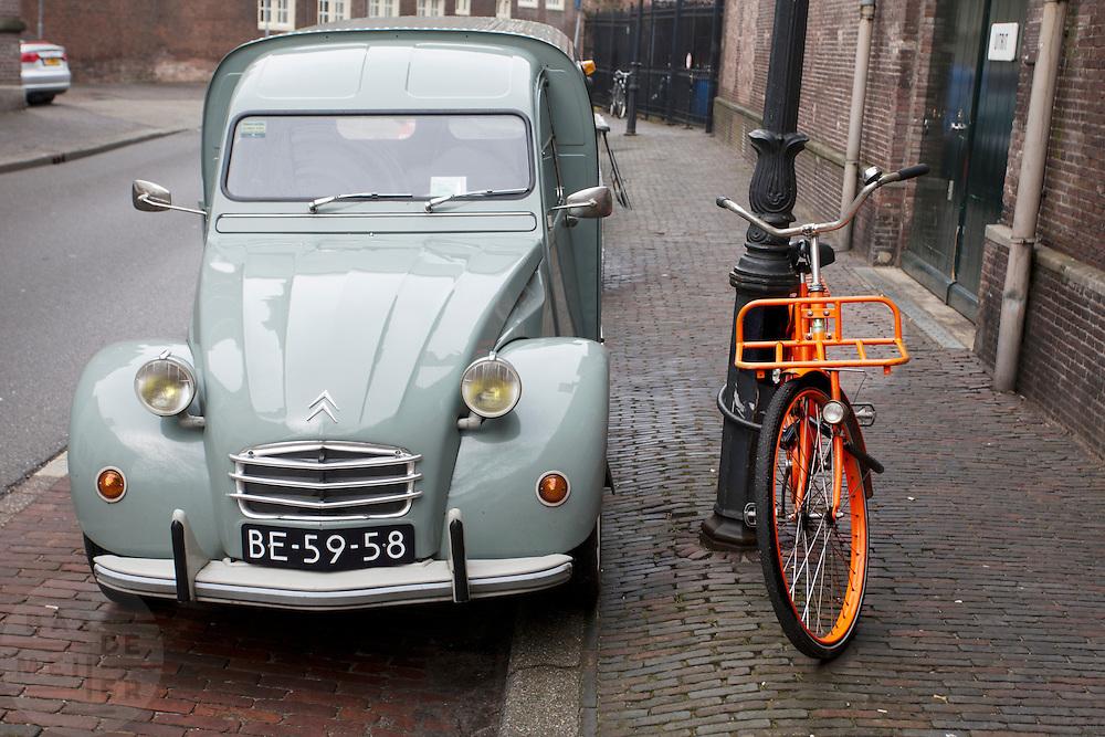 Een besteleend bij een oranje fiets.<br /> <br /> An old Acadiane is parked nearby a orange bike.