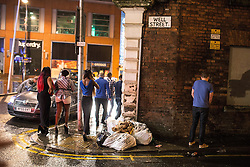 © Licensed to London News Pictures . 21/12/2013 . Manchester , UK . A man urinates against a wall on Well Street as others walk by . Christmas revellers out in the rain in Manchester on Mad Friday , the last Friday night before Christmas which is typically one of the busiest nights of the year for police and ambulance crews . Photo credit : Joel Goodman/LNP