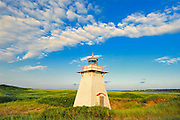 Lighthouse in sand dunes with clouds