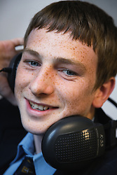 Secondary school student listening to headphones in a music lesson,