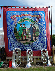 "© Licensed to London News Pictures. 13/07/2013<br /> <br /> Durham City, England, United Kingdom<br /> <br /> Instruments are placed on the floor next to a colliery banner from Trimdon Grange Colliery during the Durham Miners Gala.<br /> <br /> The Durham Miners' Gala is a large annual gathering held each year in the city of Durham. It is associated with the coal mining heritage of the Durham Coalfield, which stretched throughout the traditional County of Durham, and also gives voice to miners' trade unionism. <br /> <br /> Locally called ""The Big Meeting"" or ""Durham Big Meeting"" it consists of banners, each typically accompanied by a brass band, which are marched to the old Racecourse, where political speeches are delivered. In the afternoon a Miners' service is held in Durham Cathedral <br /> <br /> Photo credit : Ian Forsyth/LNP"