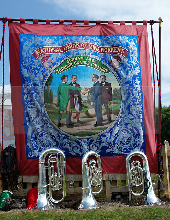 """© Licensed to London News Pictures. 13/07/2013<br /> <br /> Durham City, England, United Kingdom<br /> <br /> Instruments are placed on the floor next to a colliery banner from Trimdon Grange Colliery during the Durham Miners Gala.<br /> <br /> The Durham Miners' Gala is a large annual gathering held each year in the city of Durham. It is associated with the coal mining heritage of the Durham Coalfield, which stretched throughout the traditional County of Durham, and also gives voice to miners' trade unionism. <br /> <br /> Locally called """"The Big Meeting"""" or """"Durham Big Meeting"""" it consists of banners, each typically accompanied by a brass band, which are marched to the old Racecourse, where political speeches are delivered. In the afternoon a Miners' service is held in Durham Cathedral <br /> <br /> Photo credit : Ian Forsyth/LNP"""