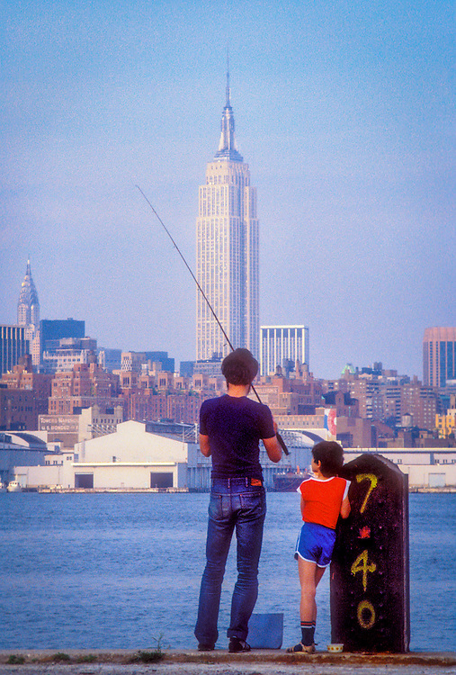 A man and boy fish from a pier on the New Jersey side of the Hudson River circa 1985 with the Empire State Building and the Manhattan skyline in the background.