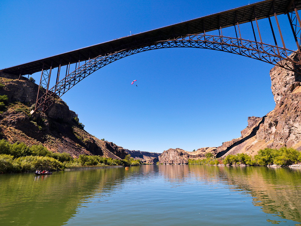 Licensing - Open Edition Prints<br /> Base jumper flies off the Perrine Bridge at 486 feet (148 m) above the Snake River in Twin Falls Idaho with a white chute on a bluebird day. The Perrine Bridge is a popular BASE jumping site known the world over. It may be the only man-made structure in the United States where BASE jumping is allowed year-round without a permit.