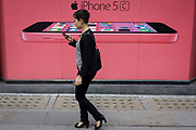 A woman walks past a phone network supplier's ad for the Apple iPhone 5c. A side profile view of the newest in the iPhone range is featured against a pink background colour, perhaps appealing more to the female buyer. Coincidentally, a woman consumer passes-by holding her own smartphone, maybe not a iPhone but one with a similar OS. The iPhone 5S (marketed with a stylized lowercase 's' as iPhone 5s) is a smartphone developed by Apple Inc. It is part of the iPhone line, and was released on September 20, 2013.