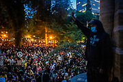 Matthew Pine, 20, of Portland, raises his fist as a sea of protesters listen to speakers during a Black Lives Matters protest near Multnomah County Justice Center in Portland, Ore. on Friday, July 24, 2020.
