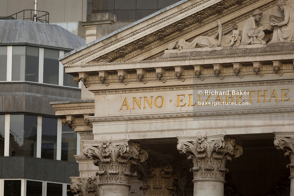 Latin inscriptions above columns with their Corinthian capitals of Cornhill in the heart of the Square Mile, the capital's historical and financial centre, on 1st November 2017, in the City of London, England. At the top of Doric and Ionic columns with their ornate stonework, powerfully strong lintels cross, bearing the load of fine artistry and carvings which feature the design by Sir William Tite in 1842-1844 and opened in 1844 by Queen Victoria whose name is written in Latin (Victoriae R).
