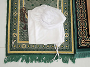Muslim Cham women's white clothing worn for praying folded up on a prayer mat at the mosque in Van Lam village, Ninh Thuan province, Central Vietnam. The Cham people are remnants of the Kingdom of Champa (7th to 18th centuries) and are recognised by the government as one of Vietnam's 54 ethnic groups. The majority of Cham in Vietnam (also known as the Eastern Cham) are Hindu but there is also a sizeable Muslim community of around 39,000 people inhabiting Ninh Thuan and Binh Thuan provinces along the coast of central Vietnam.