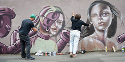 Graffiti artists 'Age Age', left, and 'Caro Pepe' work on a street level piece on a garden wall as they take part in Upfest, a street art and graffiti festival in Bristol.