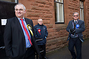 General election 2015. West Kilbride, Scotland. Observers at polling place from SNP, Labour and Conservative parties