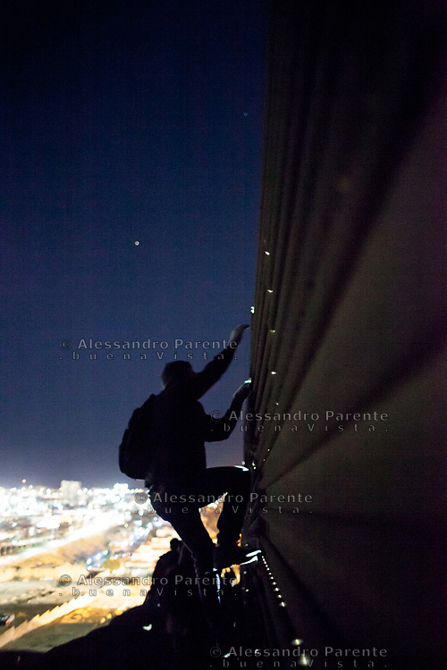 Silouette of a migrant from honduras climbing the fence at tijuana border
