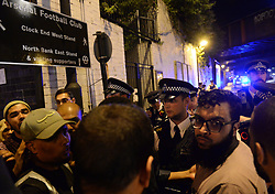 """Police officers talk with local people at Finsbury Park in north London, where one person has been arrested after a vehicle struck pedestrians, leaving """"a number of casualties""""."""