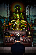 A man is praying in front of a Buddha statue in Linh Ung pagoda, Danang. Vietnam, Asia