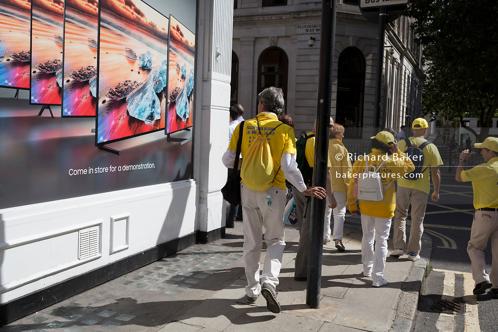 Members of the Falun Gong movement walk past an ad for widescreen televisions, on 29th August 2019, in Westminster, London, England.