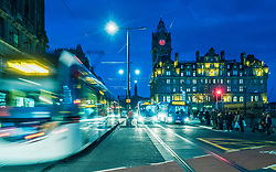 Night view of Princes Street with tram and buses and Balmoral Hotel to rear in Edinburgh, Scotland, United Kingdom.