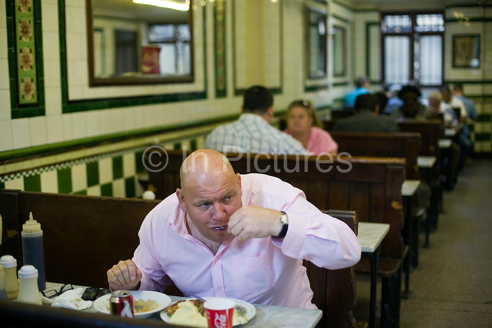 A man eats a lunch of pie, mash and jellied eels in Manze's Eel, Pie and Mash shop on Tower Bridge Road London, UK.This pie shop was opened in 1897 and is the oldest pie and eel shop in the countryEel, pie and mash shops are a traditional but dying business. Changing tastes and the scarcity of the eel has meant that the number of shops selling this traditional working class food has declined to just a handful mostly in east London. The shops were originally owned by one or two families with the earliest recorded, Manze's on Tower Bridge Road being the oldest surviving dating from 1908. Generally eels are sold cold and jellied and the meat pie and mash potato covered in a green sauce called liquor.