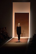 The last model, wearing a black floor length dress with V-neck and V-hem, leaves the runway at the end of the show.