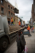 Scaffolding being delivered to a construction project on Brick Lane, London, UK. This is a predominantly Muslim area and now being developed slowly as more flats and apartment buildings are built.