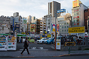 A male office worker or salaryman, wearing a face mask against the Coronavirus, walks in the backstreets of Ikebukuro, Tokyo, japan. Wednesday October 21st 2020
