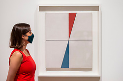 """© Licensed to London News Pictures. 13/07/2021. LONDON, UK. A staff member poses with """"Two Triangles"""", 1931.  Preview of the first UK retrospective exhibition at Tate Modern of works by Sophie Taeuber-Arp (1889-1943), one of the foremost abstract artists and designers of the 1920s and 30s. Works from Taeuber-Arp's accomplished career as a painter, architect, teacher, writer, and designer of textiles, marionettes and interiors is on 15 July – 17 October 2021.  Photo credit: Stephen Chung/LNP"""