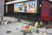 Workmen put the finishing touches to a new pavement project below a movie poster for the film Hop. As pedestrians pass-by, the workmen bend to cut the last stone within the protection of wire construction fencing that keeps the public out during this health and safety hazard. The renewal is part of the redevelopment at Elephant & Castle in south London, a notoriously bad example of post-war urban planning. The clean paving stones are untouched by inner-city feet and the landscape pristine. The film Hop is a CGI Universal Pictures production.