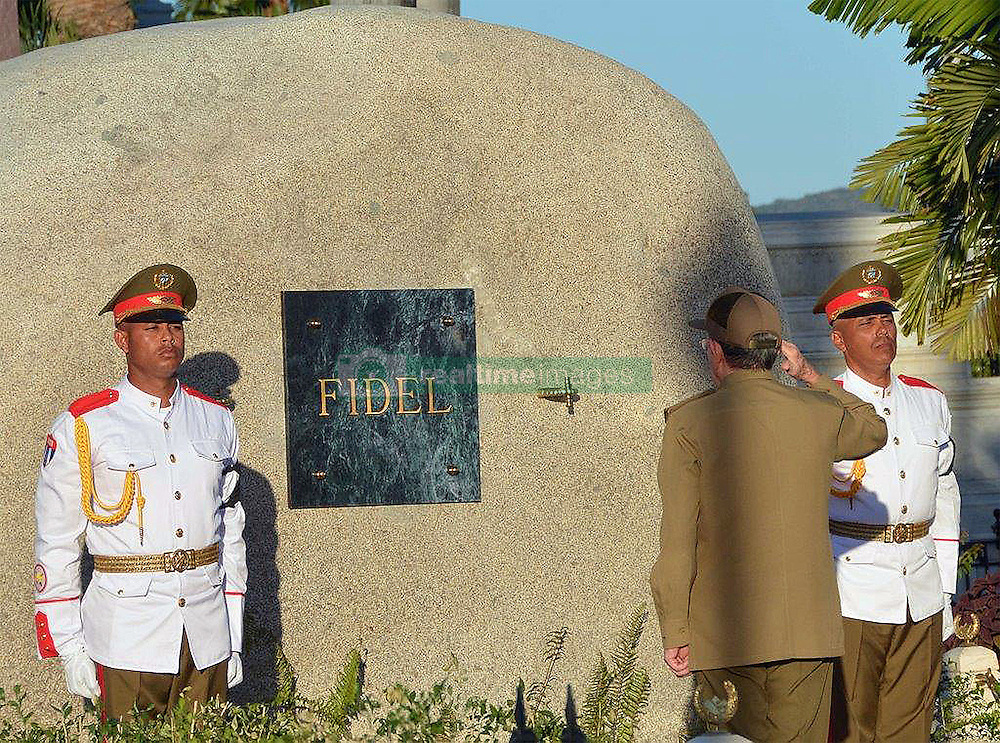 December 4, 2016 - Santiago, CUBA - Cuba's President Raul Castro salutes at the tomb of his older brother Fidel Castro, a simple, grey, round stone about 15 feet high, at the Santa Ifigenia cemetery in Santiago, Cuba, Sunday December 4, 2016. Raul Castro placed the ashes in a niche in the tomb that was then covered by a plaque bearing the single name,''Fidel. (Credit Image: © Prensa Internacional via ZUMA Wire)
