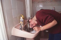 Teenage girl washing hair in bathroom basin,
