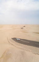 Aerial view of white car in road covered by sand in the desert, Abu Dhabi, UAE.