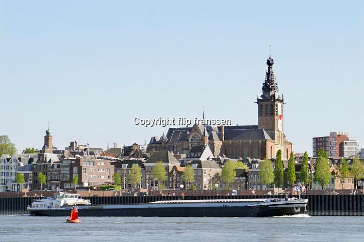 Nederland, Nijmegen, 22-4-2020 Het water in de waal zakt langzaam vanwege de aanhoudende droogte in haar stroomgebied. Binnenvaartschip vaart langs Nijmegen  . Langzaam daalt het peil van het water in de rivier .In de herfst van 2018 stond de stand bij Lobith op 6,55 meter boven nap, een laagwater record dat veel overlast voor de binnenvaart opleverde .. . Die stand is nu nog 7,80 meter . In de maas wordt vanaf zuid Limburg het waterpeil kunstmatig geregeld via de stuwen en sluizen en is pas bij minimale aanvoer vanuit belgie grote verlaging zichtbaar. Foto: Flip Franssen