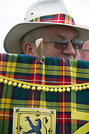 A man in a hat  behind a Buchanan tartan banner before the start of Pipefest Stirling, an event staged at Stirling Castle to coincide with the 700th anniversary of the Battle of Bannockburn. The event was attended by 1600 pipers, Highland dancers and other musicians and formed a procession through the city's streets. The Battle of Bannockburn took place in 1314 and resulted in the defeat of Edward II's English army by the Scots under Bruce.