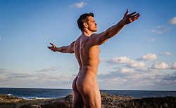 nude man at the ocean with arms up towards the sky