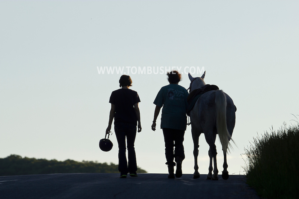 Salisbury Mills, New York - Two women walk with a horse up Otterkill Road on June 8, 2013.
