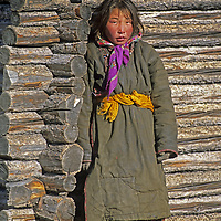 MONGOLIA, Darhad Valley. Young herder outside family's summer animal shelter.