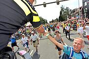 Nederland, Nijmegen, 24-7-2015Het vierdaagselegioen loopt over de Via Gladiola Nijmegen binnen. Op een van de kruispunten waar het verkeer doorgelaten wordt regelt een politieman met een helm van de Engelse Bobby het verkeer en maakt er zijn eigen show van.  Na een feestelijke intocht volgt de uiteindelijke finish en het ophalen van het kruisje, vierdaagsekruisje, op de Wedren. Iedere deelnemer krijgt een bloem, gladiool, uitgerijkt. The International Four Day Marches Nijmegen is the largest marching event in the world. It is organized every year in Nijmegen mid-July as a means of promoting sport and exercise. Participants walk 30, 40 or 50 kilometers daily, and on completion, receive a royally approved medal, Vierdaagsekruis.The participants are mostly civilians, but there are also a few thousand military participants. In 2004 a restriction on the maximum number of registrations is set to 45,000. More than a hundred countries have been represented in the Marches over the years.Foto: Flip Franssen/Hollandse Hoogte